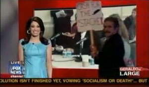 """Cash for Stash"" Sign is carried across Set as Kimberly Guilfoyle laughs and laughs."