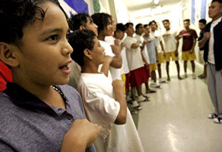 Marion, left, 12, sings the national anthem of Honduras with other children at a Texas shelter.